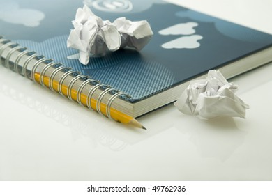 crumpled papers on notebook and yellow pencil