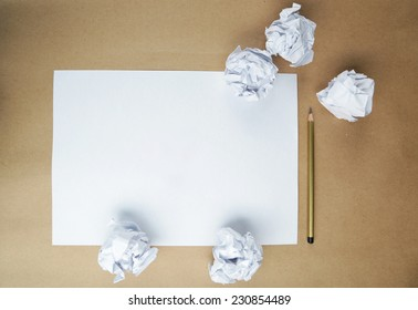 Crumpled up papers with a sheet of blank paper and a pencil on brown background