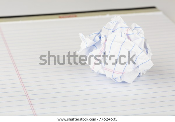 A crumpled up piece of notebook paper
