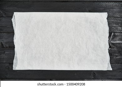 Crumpled piece of white parchment or baking paper on black wooden table. Top view. Copy space for text and design element.