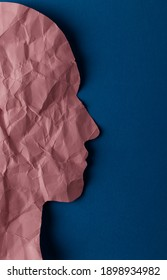 Crumpled pink paper shaped as a human head with copy space on blue paper background. Minimal concept.