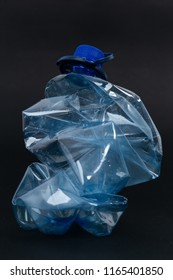 Crumpled recyclable plastic blue water beverage pet bottle as recycling single use pollution waste ecology concept isolated on black background