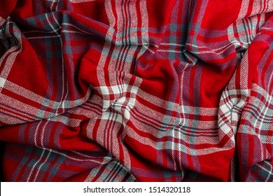 Crumpled red and blue knitted plaid. Soft and warm fabric crumpled in folds. Texture for background. Top view