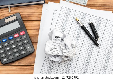 Crumpled tax form with financial documents, calculator and notepad on the table. Top view. Business concept.