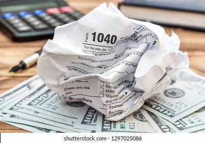 Crumpled tax form with money, calculator and notepad on the table. Close up.