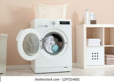 Crumpled towels in washing machine at home. Laundry room interior