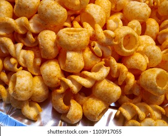 Crunchy cheese snacks puffs doodles in a serving bowl in a birthday garden party