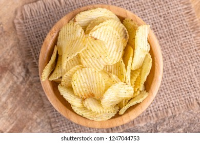 Crunchy corrugated potato chips in wooden bowl on burlap napkin. Wooden background. Junk food. Copy space