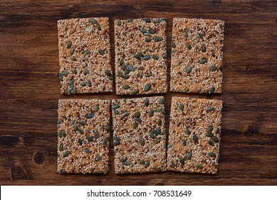 Crunchy crispbread  on a wooden background. Healthy snack: cereal crunchy multigrain cereal flax seed pumpkin, coriander, sesame, sunflower seeds protein bread bar. Protein albumin source.