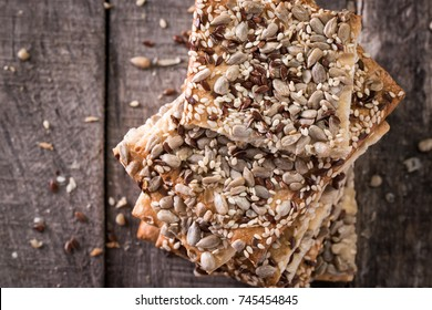Crunchy crispbread on a wooden background. Healthy snack: cereal crunchy multigrain cereal flax seed ,sesame, sunflower seeds protein bread bar.