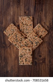 Crunchy crispbread on a wooden table. Healthy snack: cereal crunchy multigrain cereal flax seed pumpkin, coriander, sesame, sunflower seeds protein bread bar. Protein albumin source.