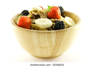 Crunchy delicious looking bran flakes and juicy fruit in a wooden bowl on a white background