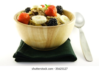 Crunchy delicious looking bran flakes and juicy fruit in a wooden bowl with a spoon and a black napkin on a white background