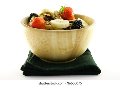 Crunchy delicious looking bran flakes and juicy fruit in a wooden bowl and a black napkin on a white background
