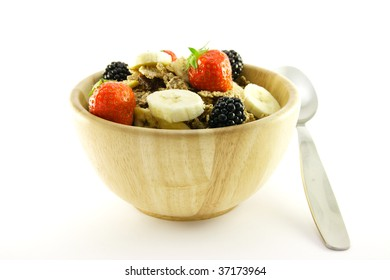 Crunchy delicious looking bran flakes and juicy fruit in a wooden bowl with a spoon on a white background