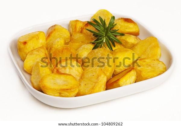 Süßigkeiten aus goldenen Kartoffeln in einer weißen Schüssel, mit Rosmarin. Keine Isolation.