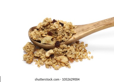 Crunchy granola, muesli pile with banana, pineapple slices, peanuts and raisins in wooden spoon isolated on white background
