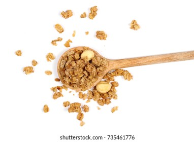 Crunchy granola, muesli pile in wooden spoon with nuts isolated on white background, top view