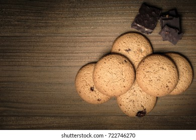Crunchy malt cookies and chocolate on dark old wooden table, Top view with copy space for text.