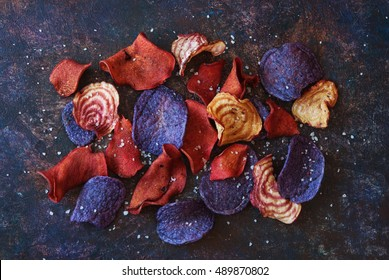 Crunchy organic dry vegetable chips and beetroot chips with salt served as a finger food snack on a desk