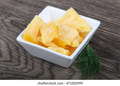 Crunchy parmesan cheese in the bowl on wood background