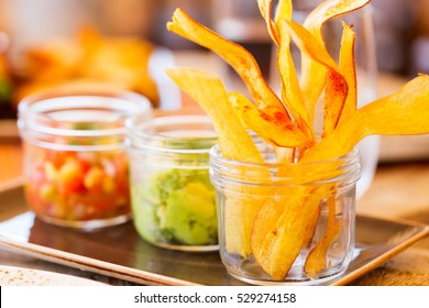 crunchy plantain chips served in glass jar with salsa and guacamole, snack or appetizer, delicious and colorful