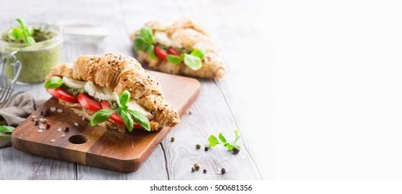 Crunchy wholegrain croissants with mozzarella, tomato and homemade pesto sauce on rustic white wooden background, selective focus