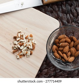 crushed almonds  on a cutting board,knife,vase with whole almonds.