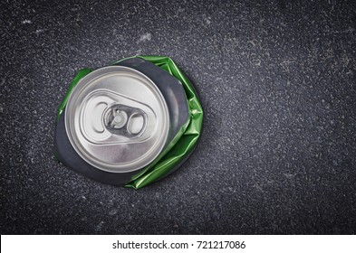 Crushed aluminium beer can on asphalt street background