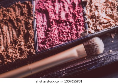 crushed blush and bronzer powders with brush close-up shot, concept of beauty and make-up products
