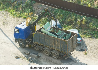 Crushed car being picked up by a grabber. An accident car has been loaded onto a dumptruck by crane. loader crane machine loading car on itself