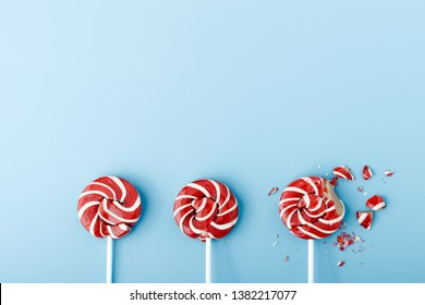 Crushed colorful candy lollipop on blue background. Colored lollipop on a blue background.Color candy on a blue background.Red and white spirals on lollipop.Trendy pop art style photo.Flat lay.