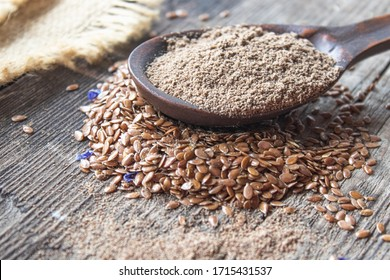 Crushed flax seed in a wooden spoon on a pile of flaxseed. Ground seed is used to prevent heart disease and being overweight.