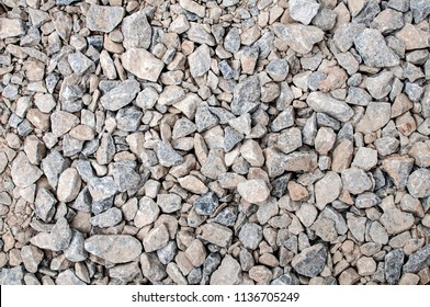 Crushed gray and beige gravel for pavement foundation closeup as background
