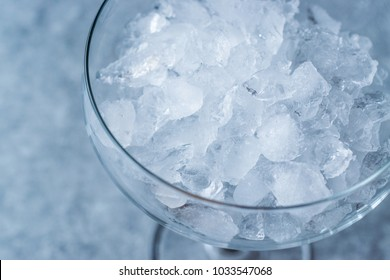 Crushed Ice in Cocktail Glass on Blue Surface.