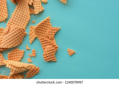 Crushed ice cream waffle cones on pastel blue background, top view flat lay modern minimal composition