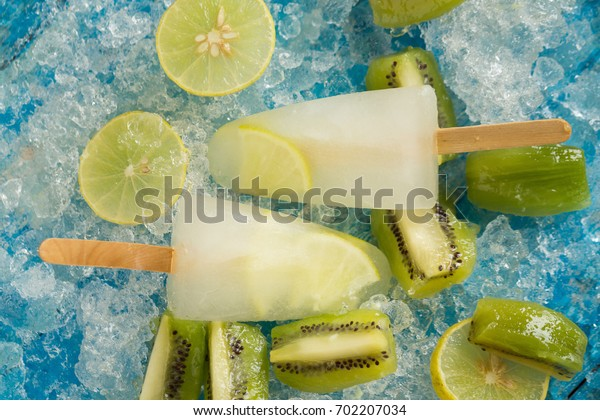 Crushed ice cubes and lemon, kiwi, homemade ice cream on vintage blue wooden table. Top view.