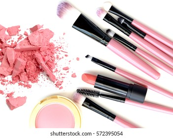 Crushed make up powder and lipstick samples with brushes on white background