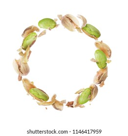 Crushed pistachios in a circular motion on white background