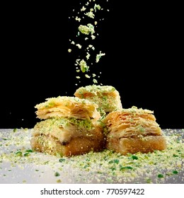 Crushed pistachios flow over three pieces baklava on a metal table