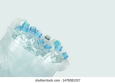 Crushed plastic bottles in the bag on gray background. Recycling concept. Eco problem