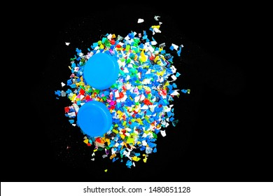Crushed plastic granules for recycling,  Crushed plastic granules isolated on black background. The concept of recycled plastic used.