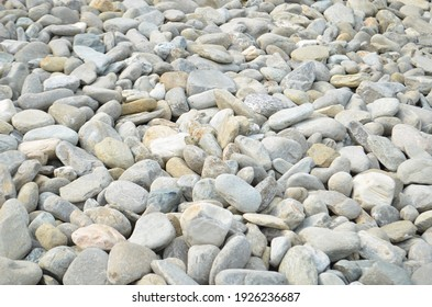 Crushed stone on the seashore. Selective focus on object. The stones were laid on the ground in the garden as a background. Background blur. Pebble stones background. Selective focus.