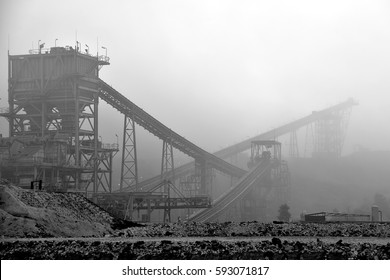 Crusher and conveyor belt in mining industry. this photo took in foggy to show in the shade of grey color.