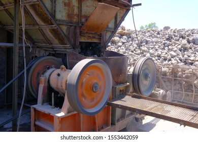 Crushing machinery, cone type rock crusher, conveying crushed granite gravel stone in a quarry open pit mining. Processing plant for crushed stone and gravel. Mining and Quarry mining equipment.