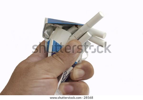 Crushing a packet of cigarettes, symbolising the struggle to beat nicotine addiction.