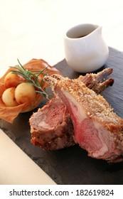 crusted lamb chop dinner on slate platter
