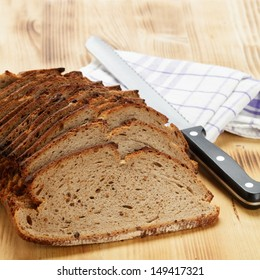 Crusty bread with knife on wooden board