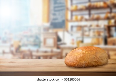 Crusty fresh bread on wooden table in bakery shop.