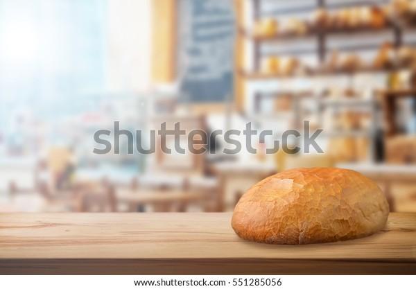 Crusty fresh bread on wooden table in bakery shop.